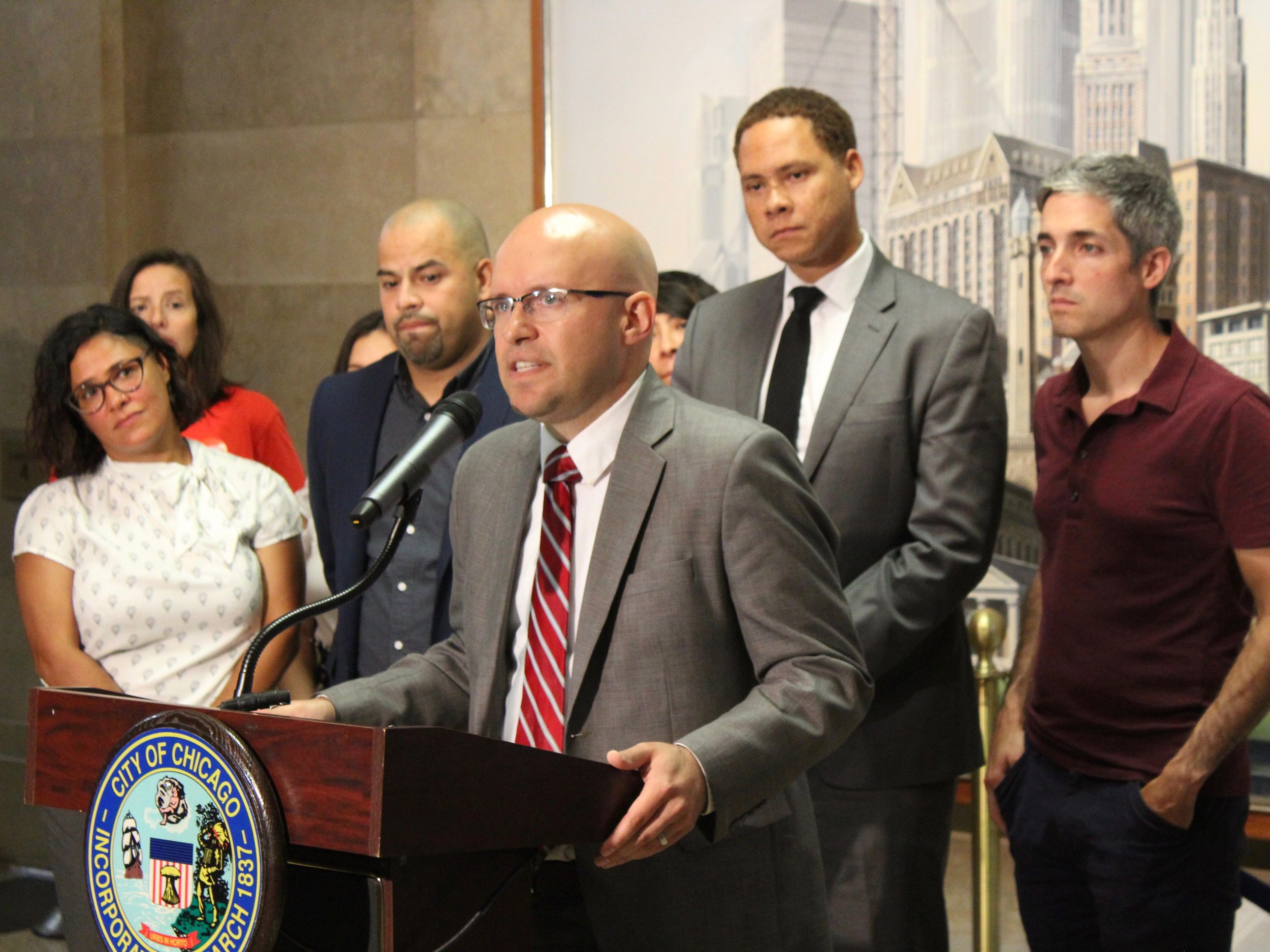 Backed by Chicago City Council colleagues Rossana Rodriguez, Andres Vazquez, Matt Martin, and Daniel LaSpata, Alderman Michael Rodriguez says anxiety over ICE raids has hurt local businesses in his Little Village neighborhood. (One Illinois/Ted Cox)