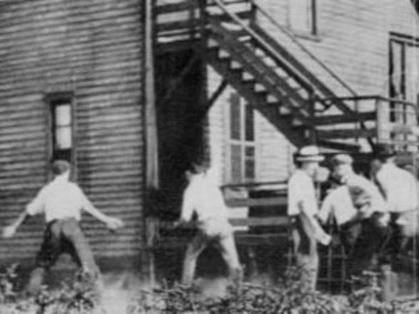 A white mob brandishes stones in pursuit of someone unseen during the 1919 Chicago race riots. The photo is in the public domain, although the Chicago History Museum credits it to Jun Fujita.