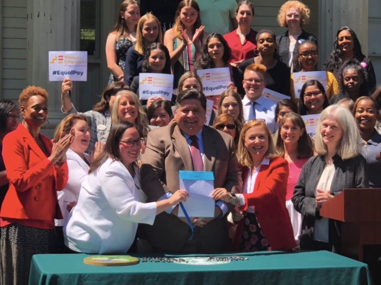 Gov. Pritzker brandishes the new bill signed into law banning employers from asking potential hires about their salary history. (Twitter/GovPritzker)