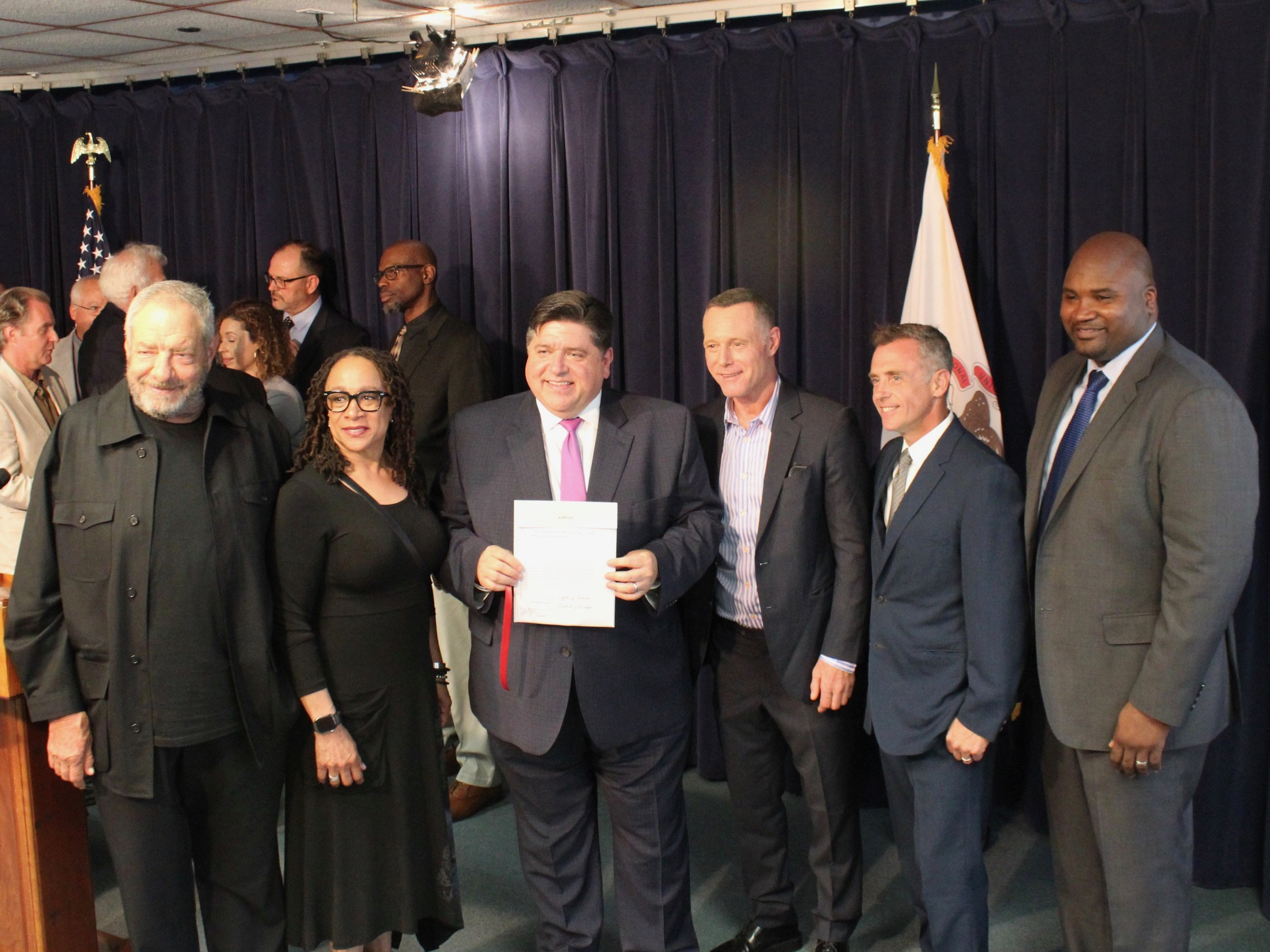 """Gov. Pritzker brandishes extension of the film tax credit, joined by state Sen. Elgie Sims (right) along with TV producer Dick Wolf and actors S. Epatha Merkerson of """"Chicago Med,"""" Jason Beghe of """"Chicago P.D.,"""" and David Eigenberg of """"Chicago Fire."""""""