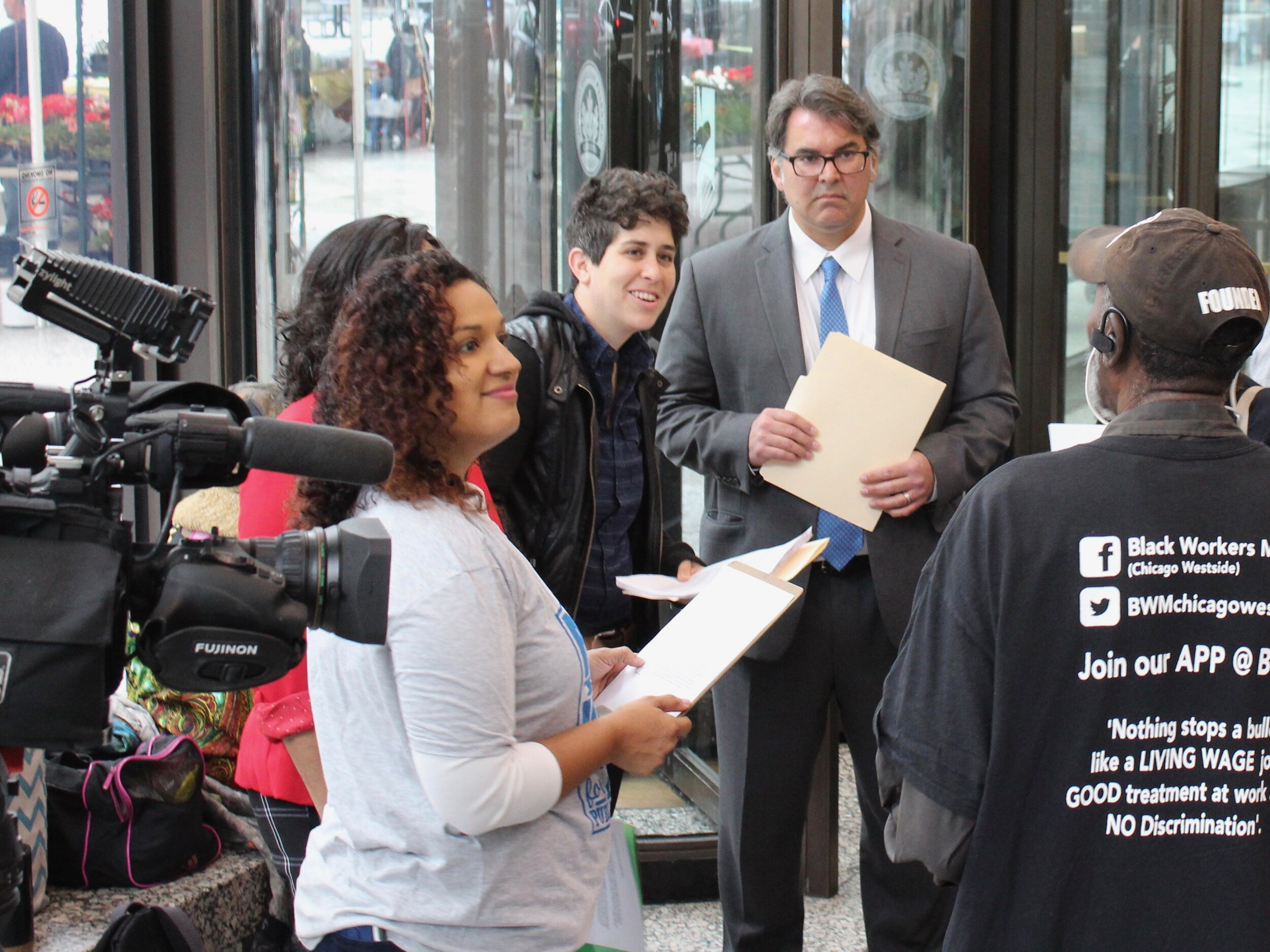 Timna Axel and Aneel Chablani (center), of the Chicago Lawyers' Committee for Civil Rights, discuss the suit before a news conference in Chicago in June. (One Illinois/Ted Cox)