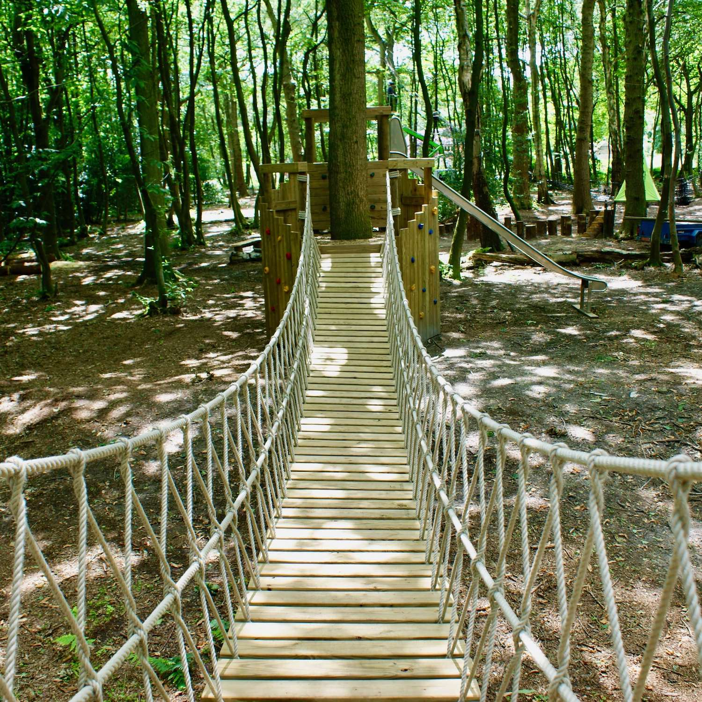 """...woodland rope bridge leading to platform deck"""