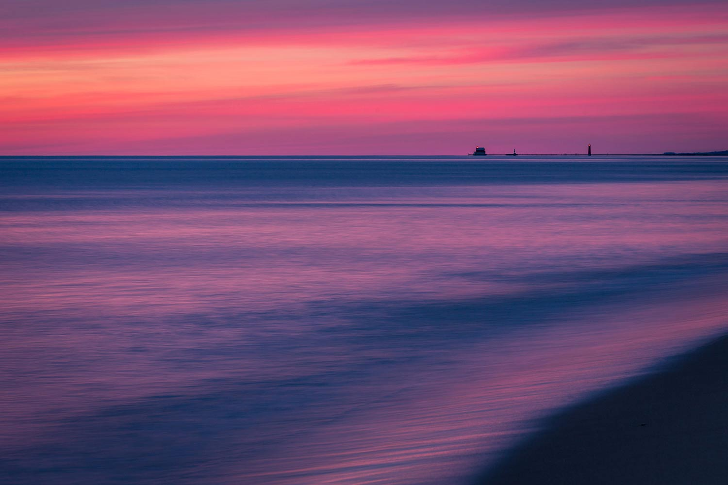 Pastel colors reflecting on the waters of Lake Michigan, with the Grand Haven light house in the distance.