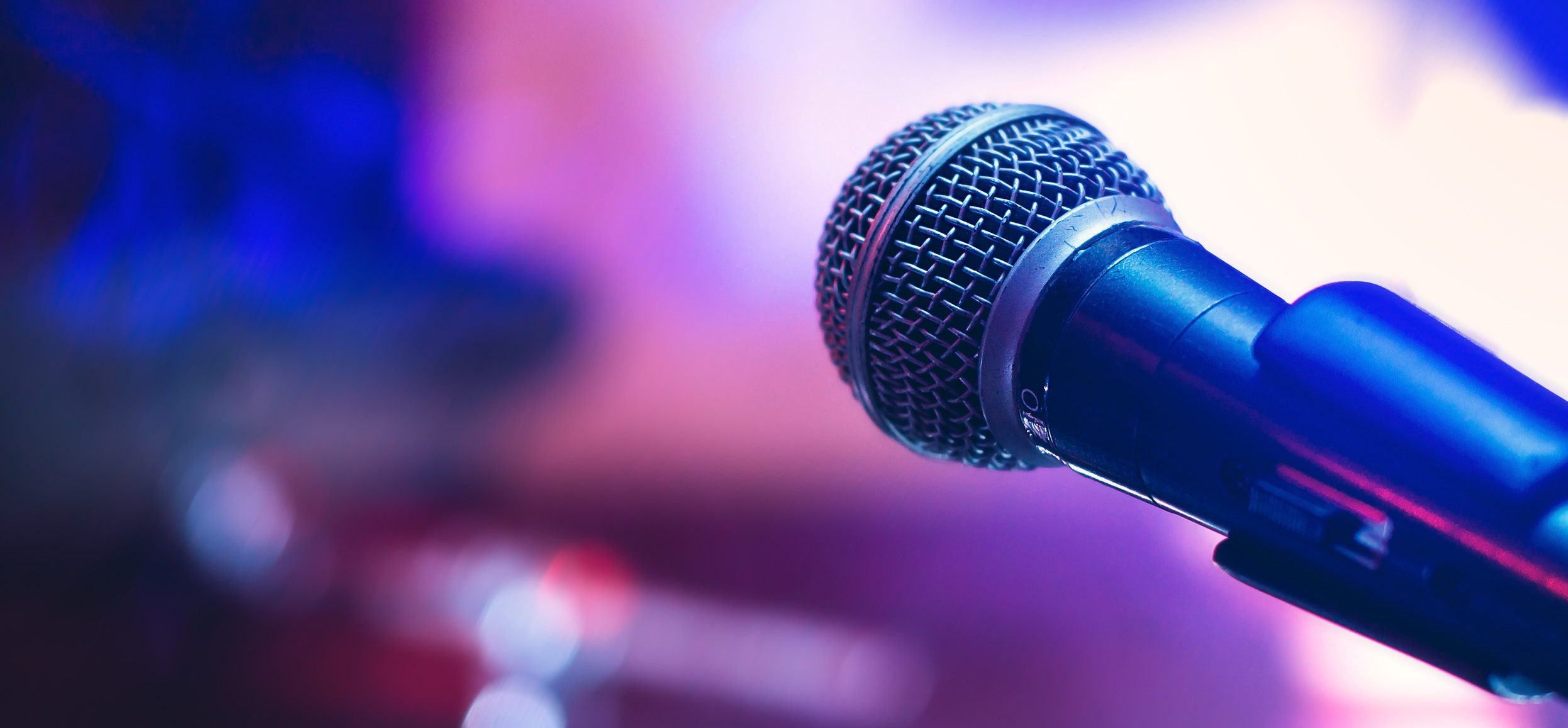 Image: A microphone in front of a purple background.