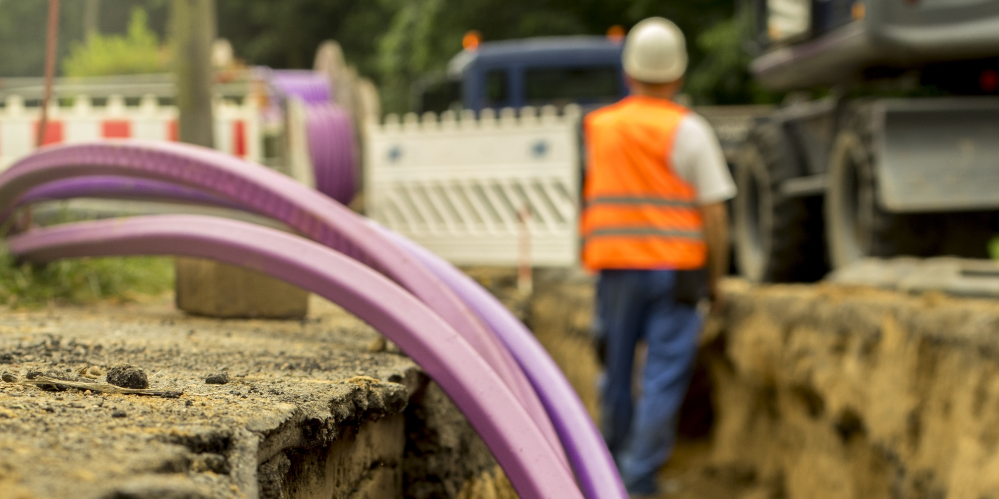 Image: A construction worker stands in a waist-high ditch. Purple cables are in the foreground.