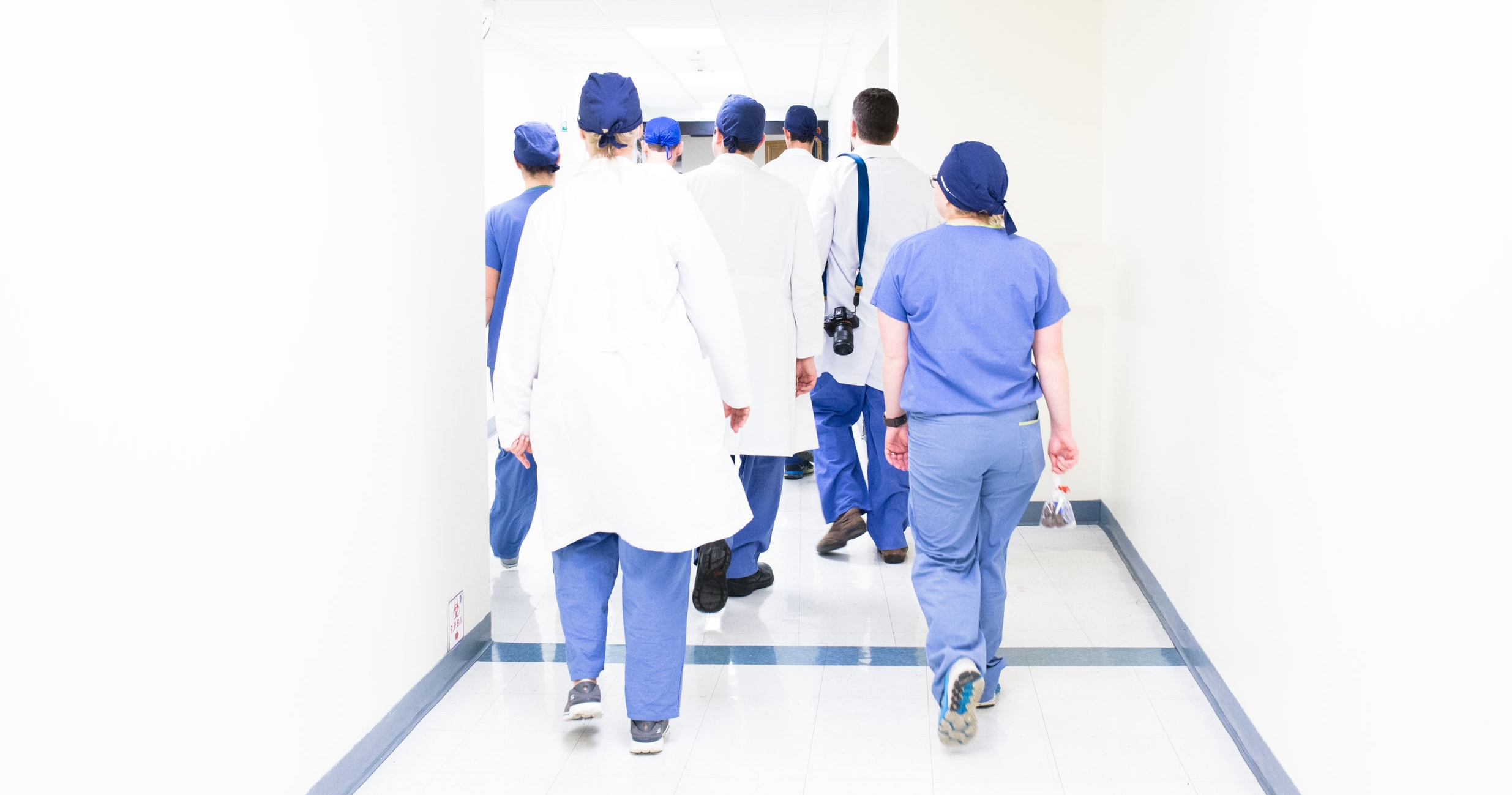 Image: Doctors in purple and white scrubs walking away from the camera down a hospital hallway.