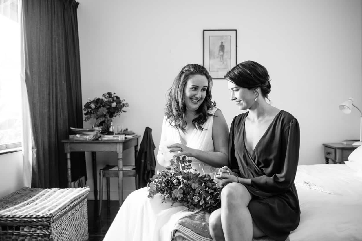 Bride sitting on a bed talking to a bridesmaid at a Brixton Wedding