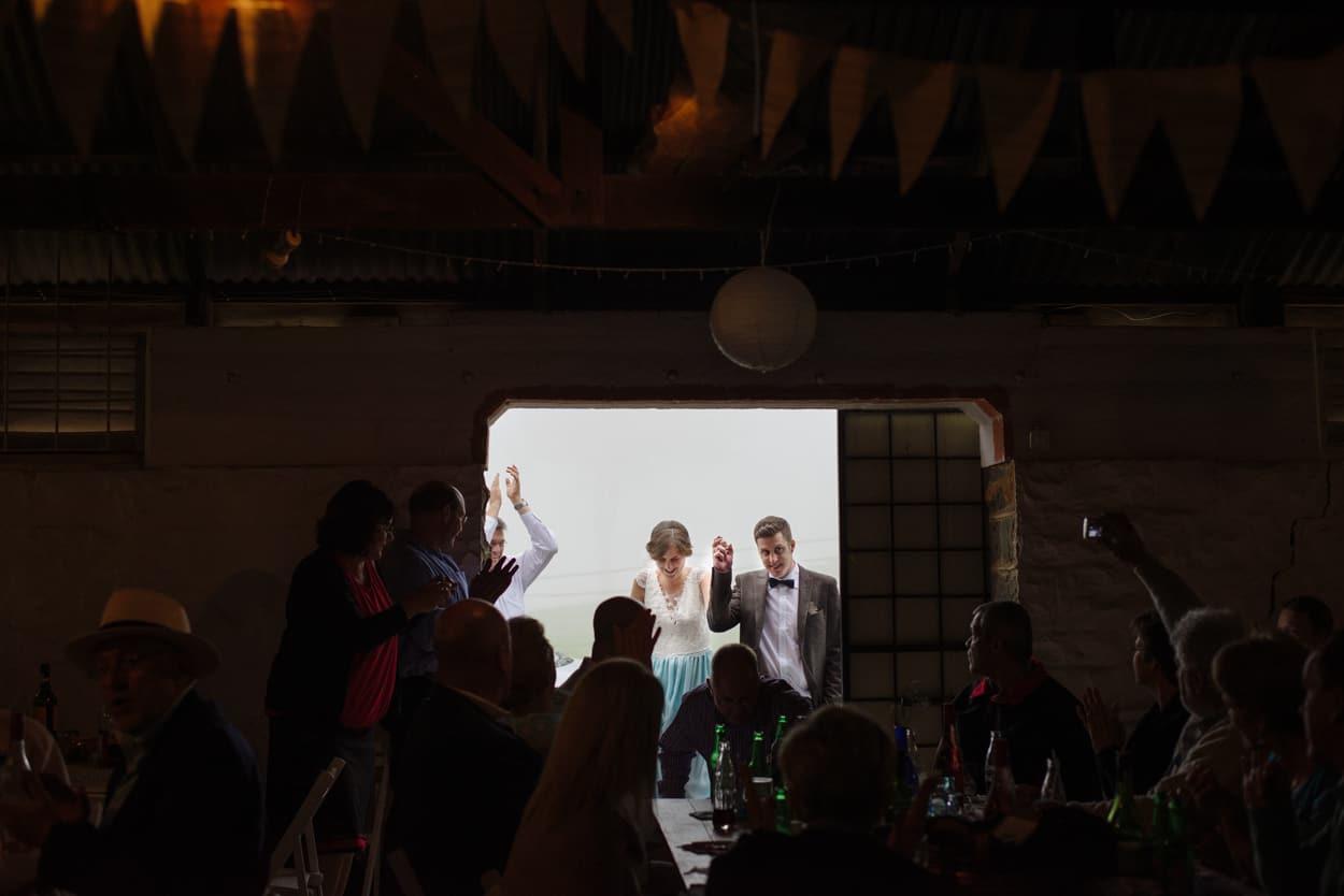 Couple enter their barn wedding reception holding hands