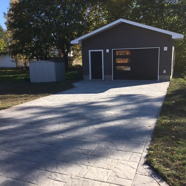 Appian Driveway with storm drainage at garage with french draining system.