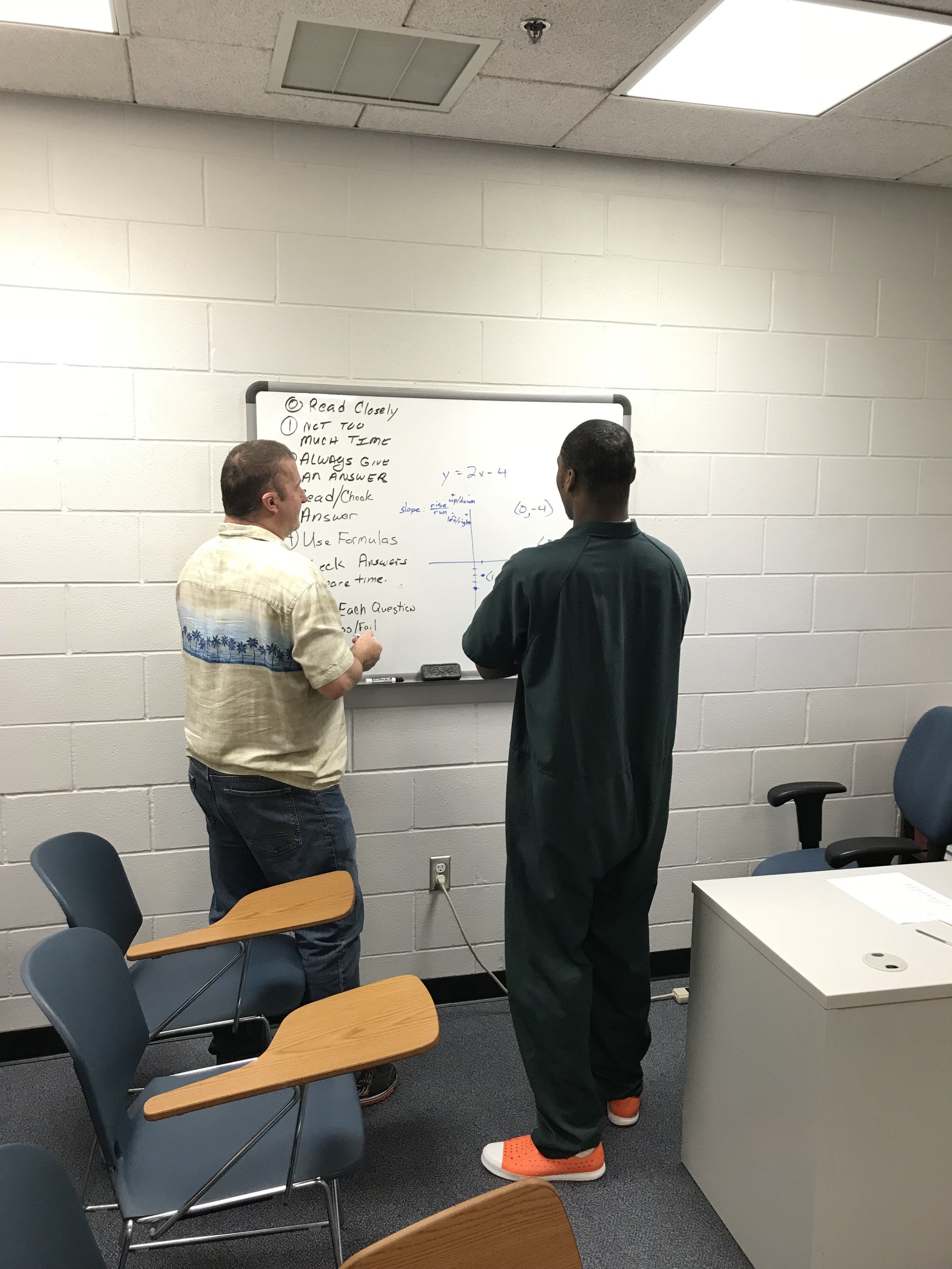 Photos provided by CCSO.Inmate with a volunteer math tutor during a GED class.