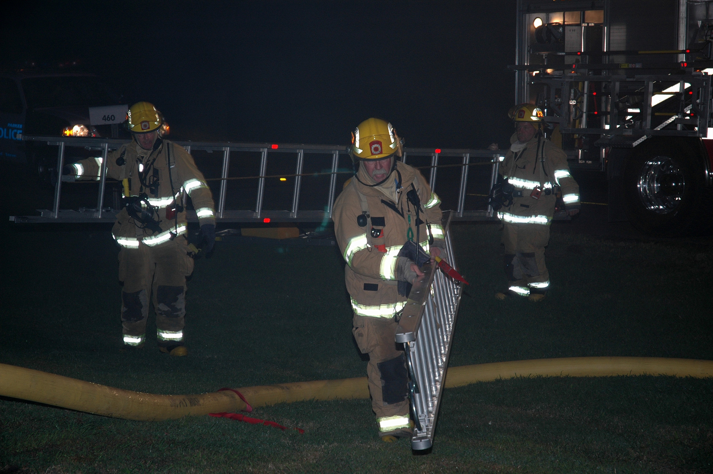 , David Leonard, center, carrying a roof ladder at a structure fire
