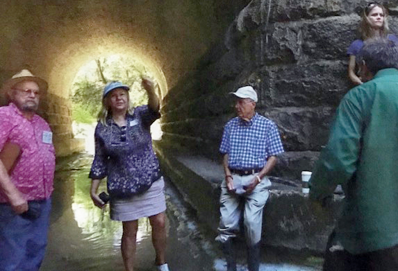 Local historian, Lindy Fisher points to the inside of the bridge in Fairview's Houston and Texas Central Railroad Historic District during the dedication in 2012 of the site as a State Archaeological Landmark. Noted historian Ken Byler is to her left.
