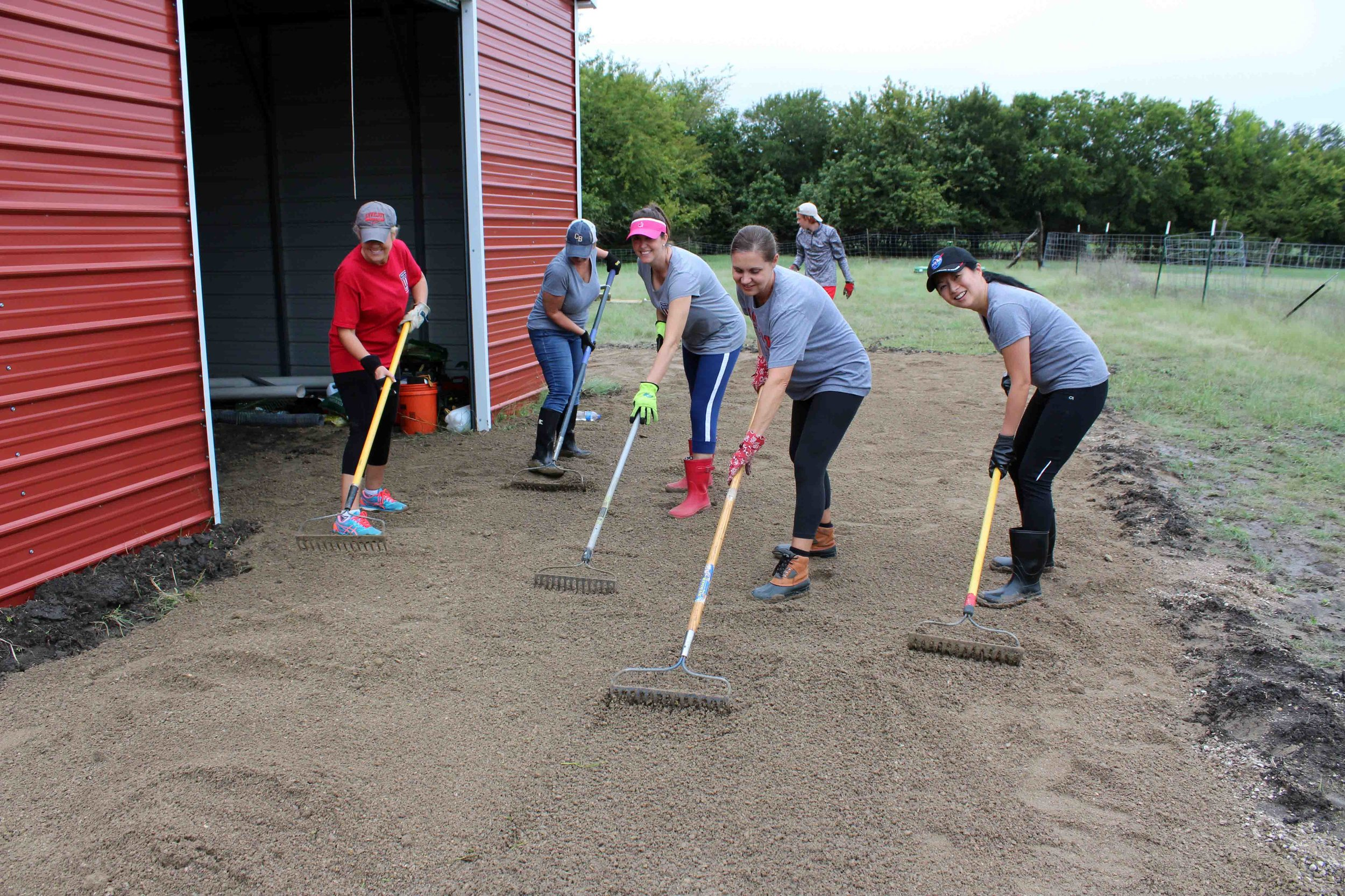 YMSL moms spread the gravel for the newly created gravel road.