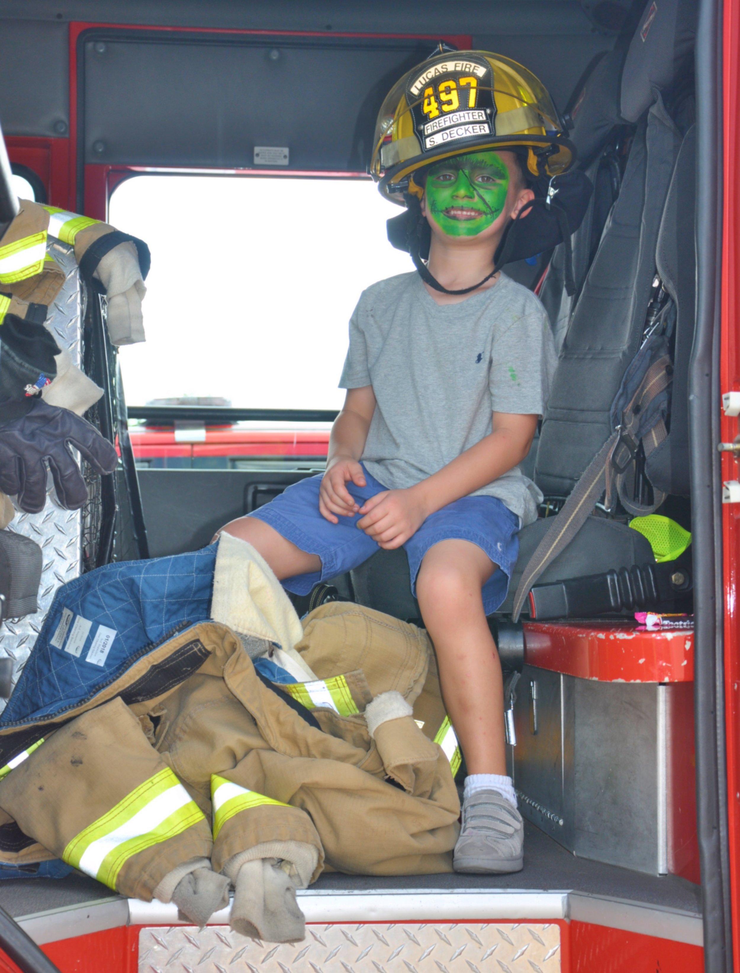 """""""Frankenstein"""" wears firefighter gear in the back of a fire truck."""