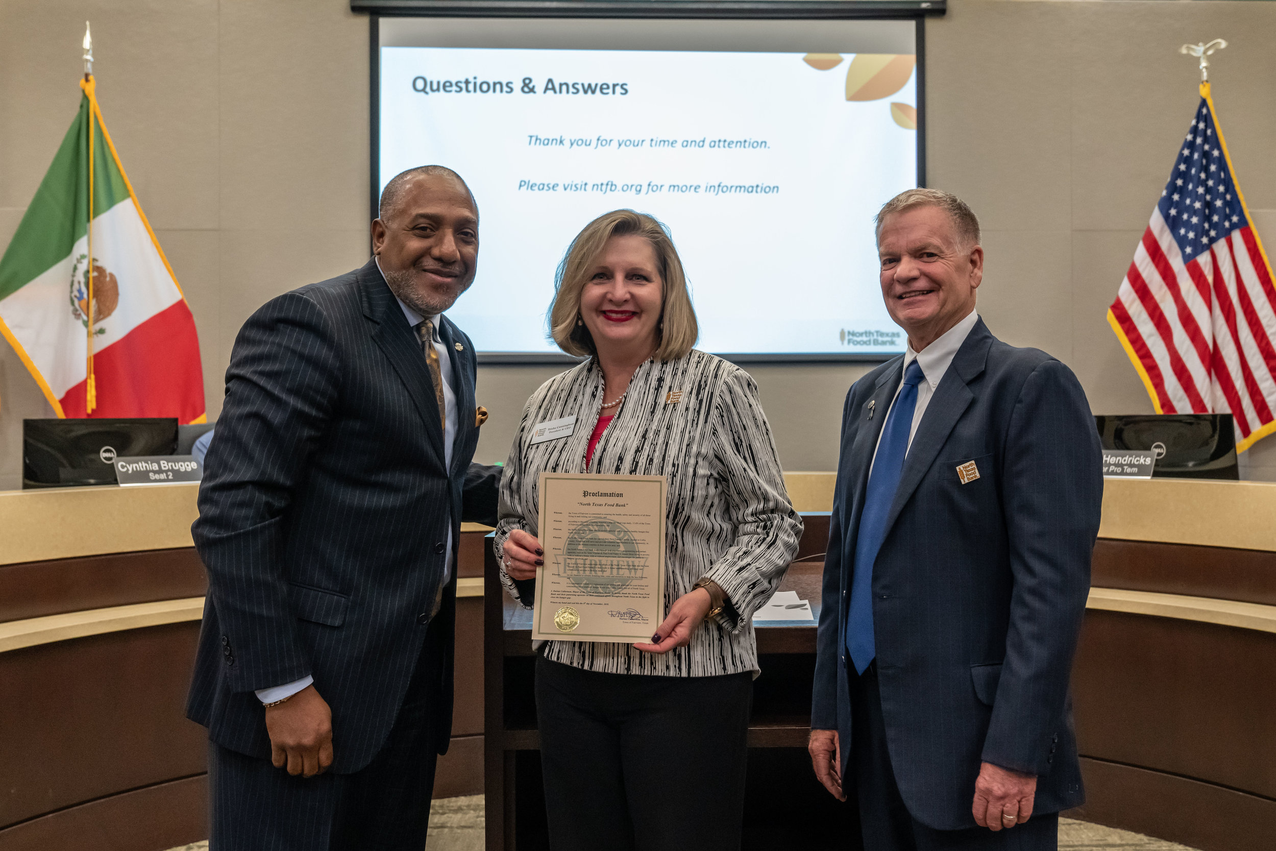 Mayor Darion Culbertson (L), presents Trisha Cunningham, CEO, North Texas Food Bank and William Carnegie, NTFB Board (R) with proclamation declaring November 8-16 Hunger and Homeless Awareness Week Fairview.