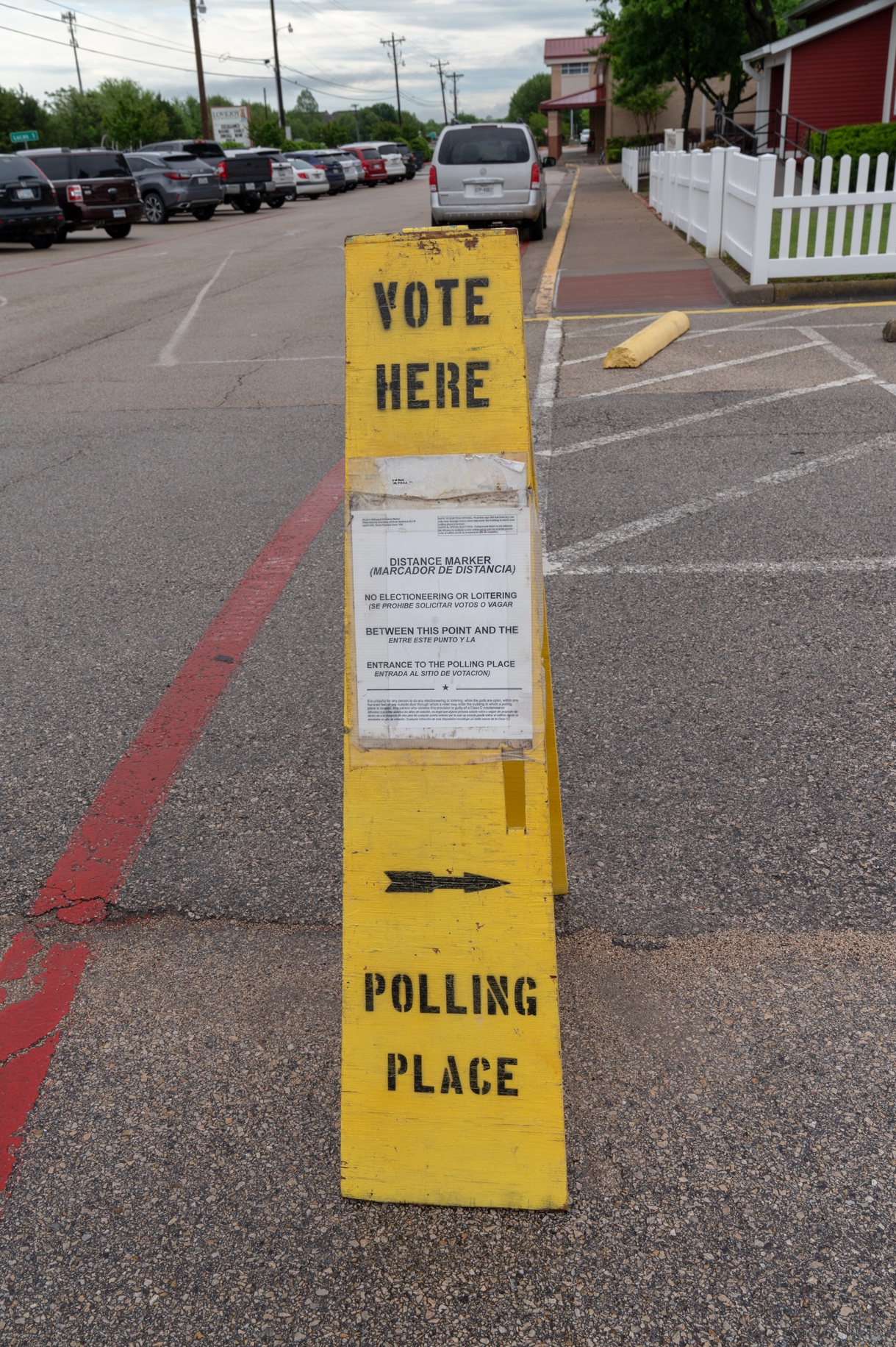 "Election judges and their clerks prepare the inside and outside of polling places to conform exactly to election law. In the case of this parking lot marker, it delineates the ""no cross"" line beyond which electioneering is prohibited."