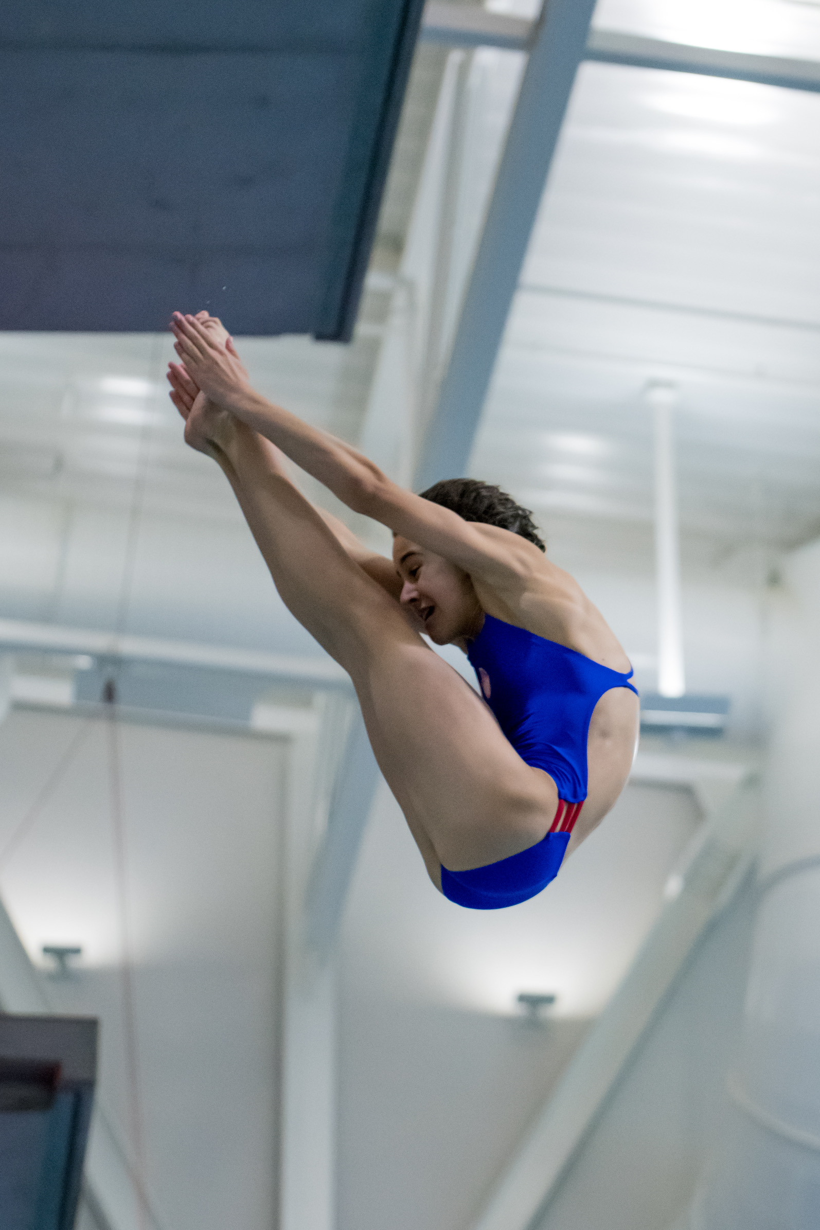 Maria is doing a 201b, a back-dive pike, on the 3-meter platform.