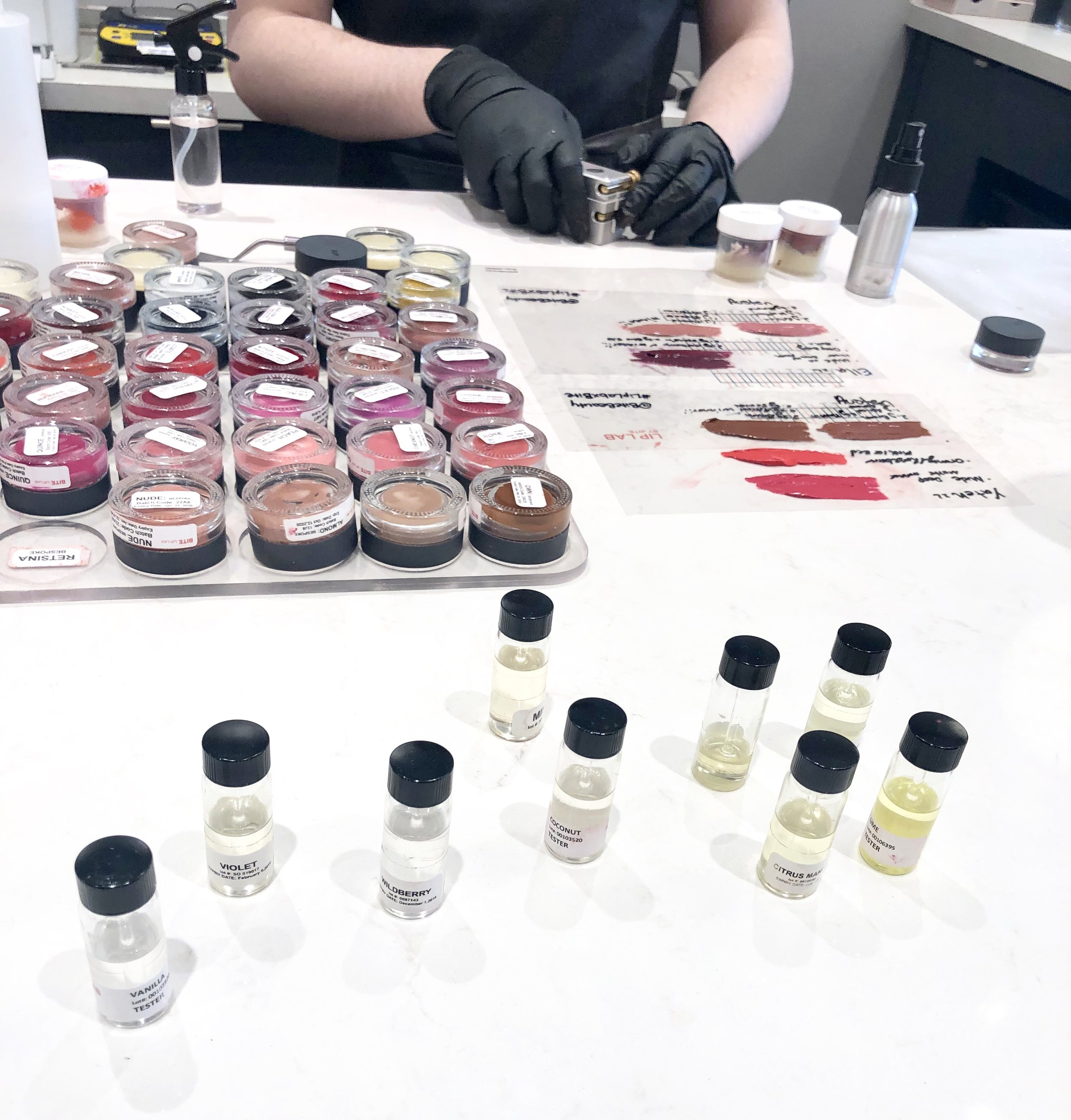 The colourful jars are the lipstick pigments that the Colour Artist mixes together to create your bespoke lipstick and the tiny jars with liquid in them are scents that you can choose to add to your lipstick as well.