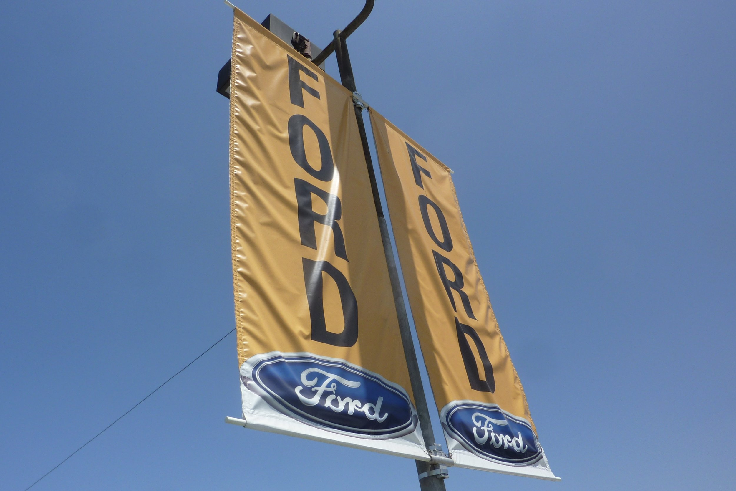 Pole banners - banners with pockets sewn in top and bottom, installed onto brackets attached to a parking lot light pole (typically) - are a great option to use that parking lot real estate you already have.