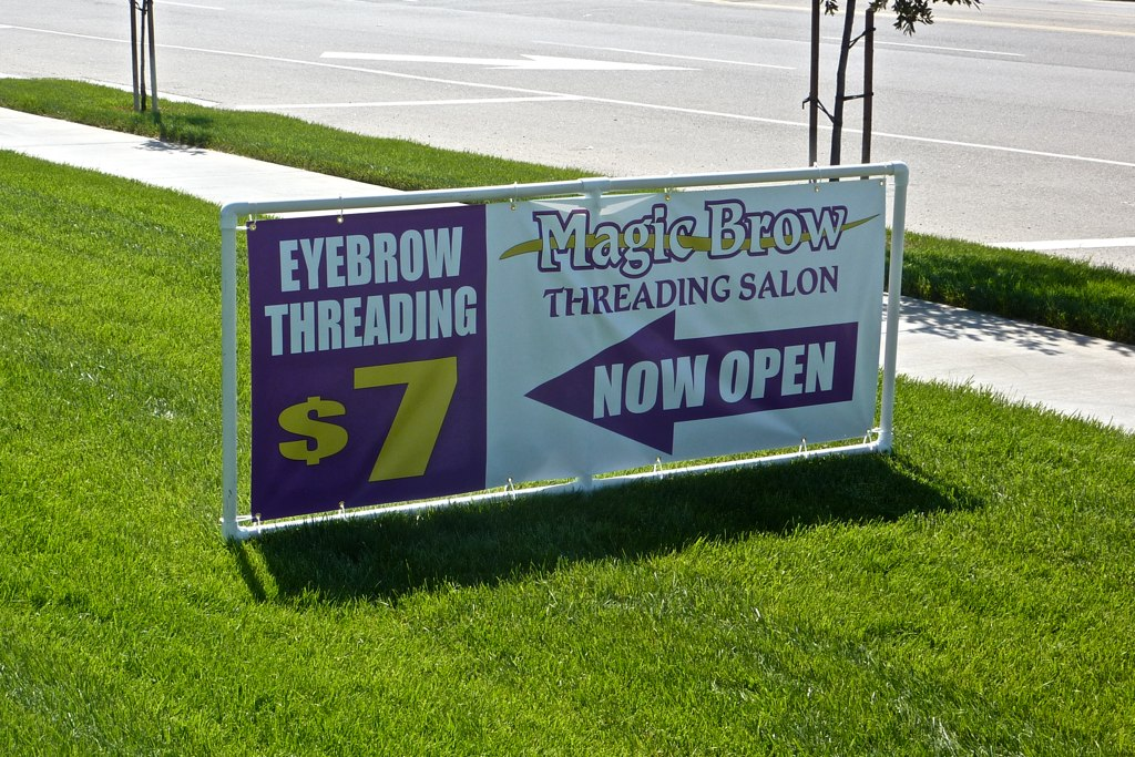 Two-sided banner attached to a lawn-mounted simple PVC frame