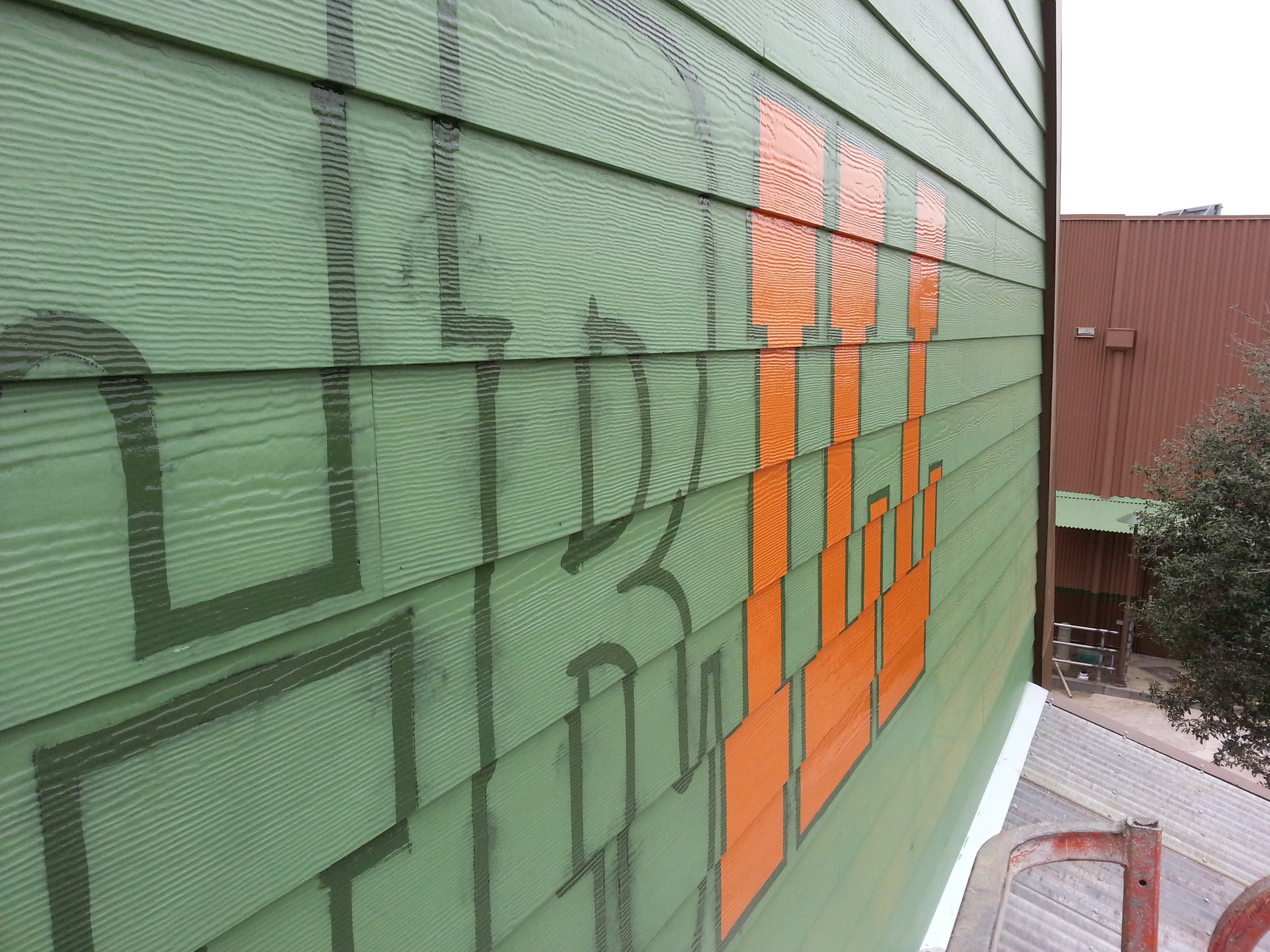 Smokejumpers Grill, California Adventure, Anaheim CA - exterior hand painted graphics - progress… the orange color being painted.
