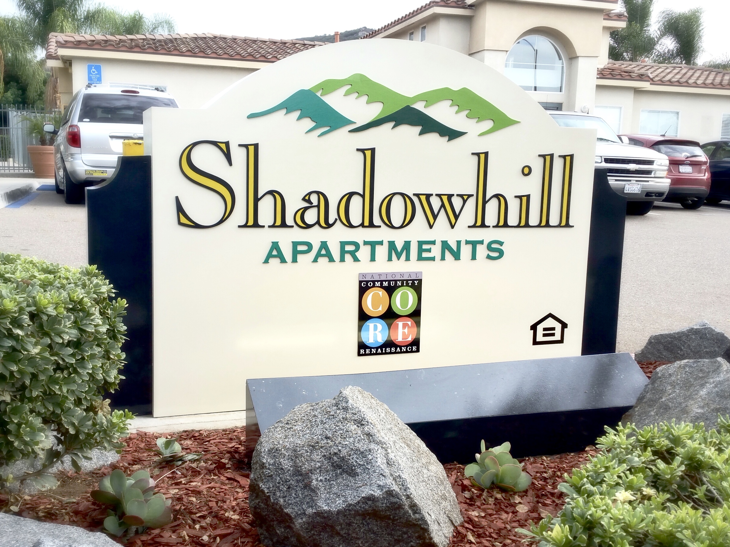 """Shadowhill Apartments monument sign is a refurbishing project in Santee, near San Diego. The aluminum letters and logo pieces were removed, sanded and repainted. The aluminum base cabinet was also completely sanded and repainted. New bright yellow vinyl details were applied to the """"Shadowhill"""" letters… then the whole sign was carefully reassembled."""
