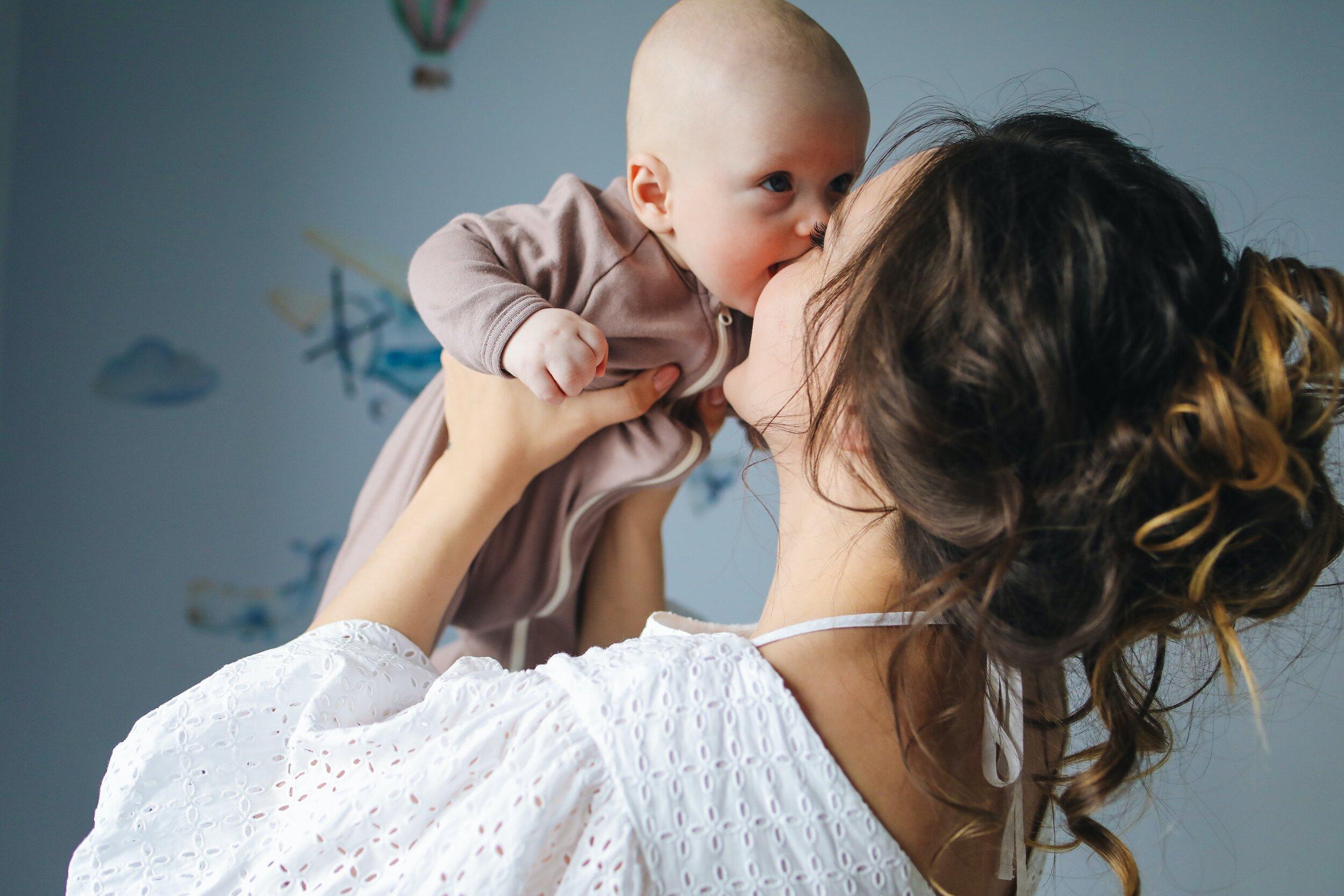 woman-in-white-top-carrying-baby-in-brown-onesie-3875225.jpg