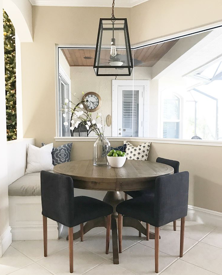 After - I chose a round table with navy accent dining chairs to make the space beautiful and functional. The throw pillows and bench cushion were recovered for a clean and fresh look. I also updated the busy chandelier with a sleek pendant.