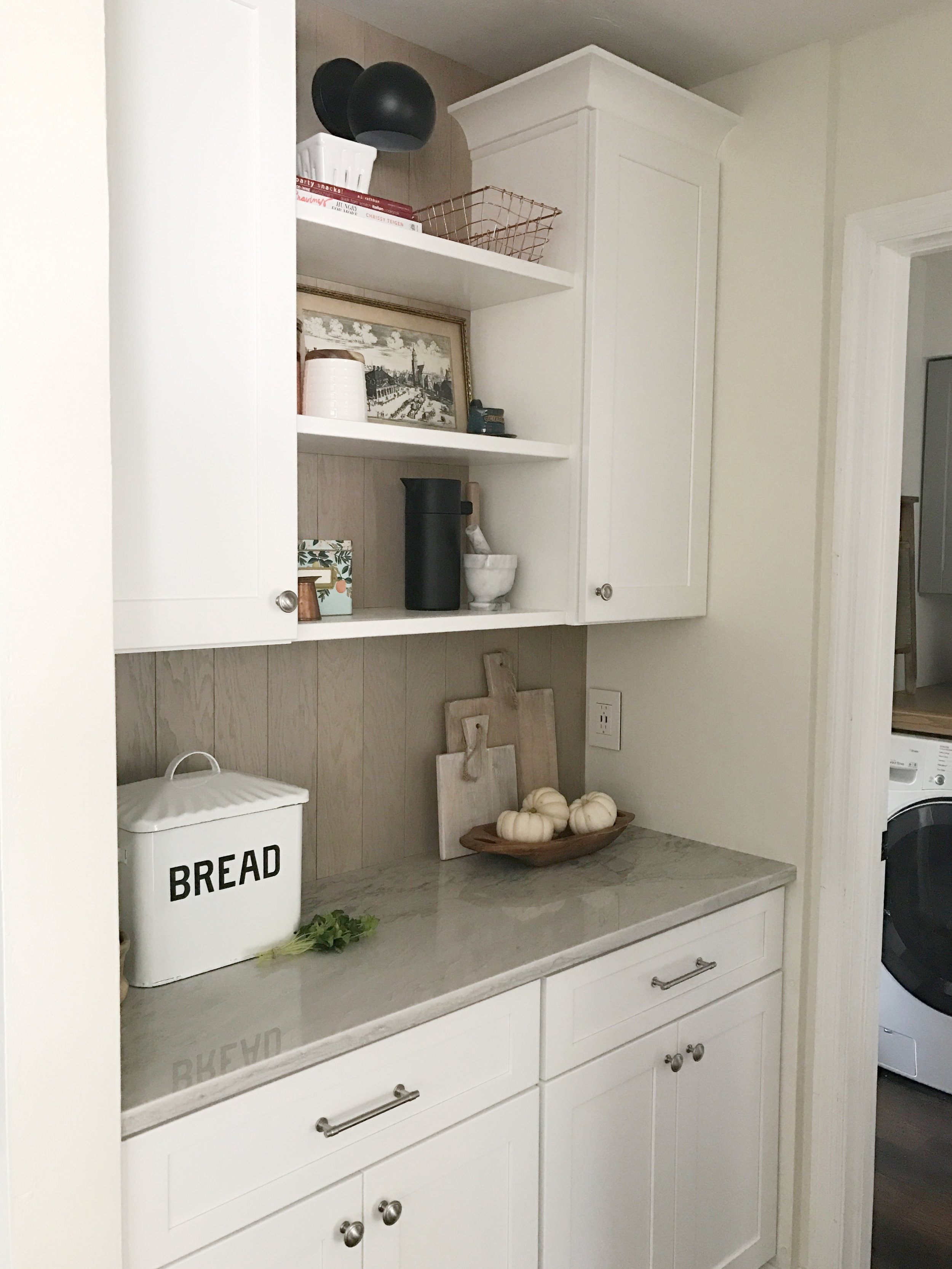 AFTER- pretty countertops and floating shelves replace a basic wire shelf pantry. I can't believe its the same little space.