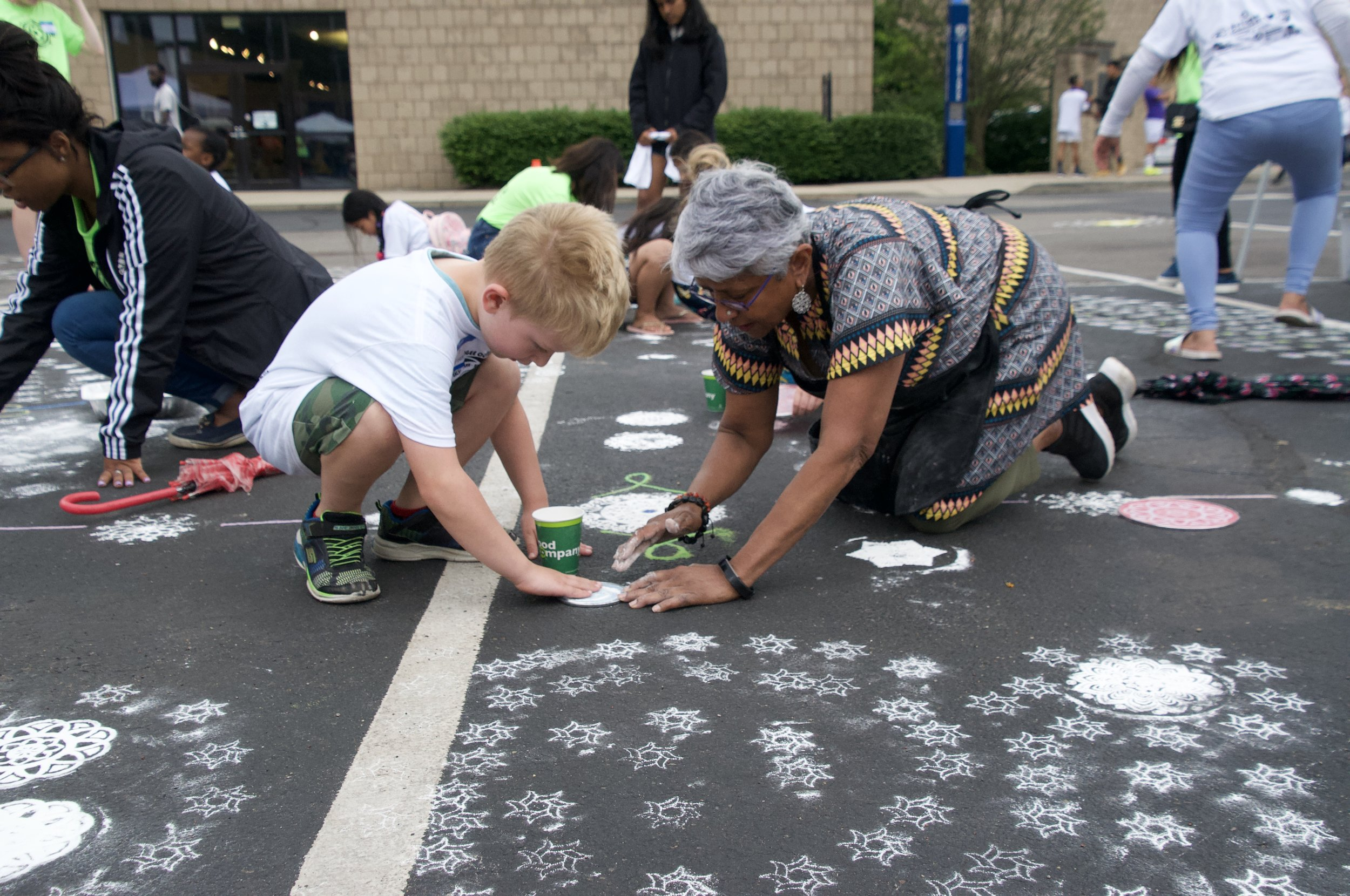 Artist Radha Lakshmi makes rice flour mandalas with participants at Refugee Connect's World Refugee Day Cup