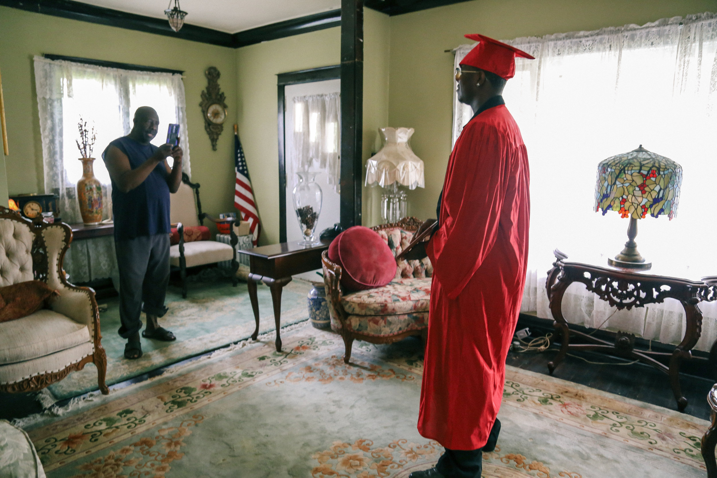 """""""Pops,"""" also known as Mr. Willis snaps a shot of his foster son Anthony Smith after he got home from receiving his high school diploma. Smith is one of 26 graduating seniors that make up Robeson's 2018 class. They are the last seniors that can say they graduated from the 40-year-old school. Photo: Olivia Obineme"""