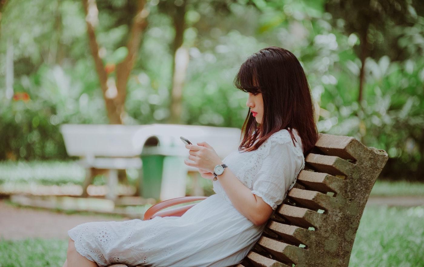 woman-sitting-on-bench-scrolling-social-media