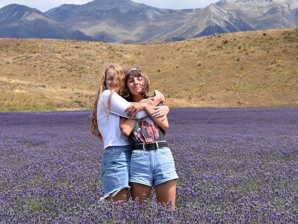 two-friends-hugging-in-field-of-flowers