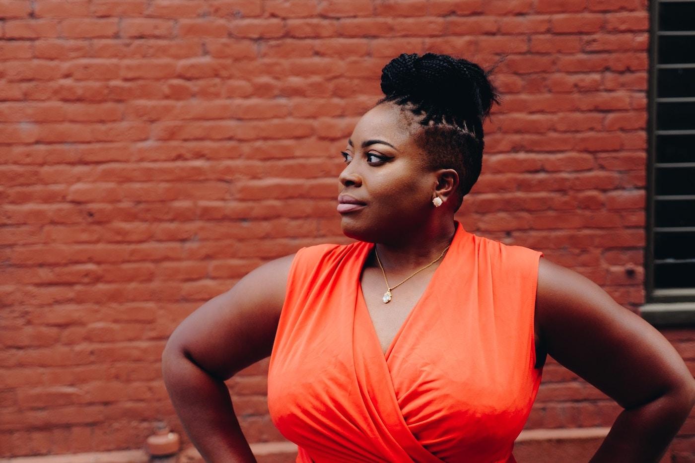 woman-orange-dress-brick-wall-15-bible-verses-for-hard-times
