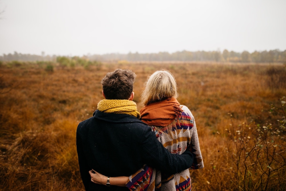 couple-hugging-in-a-field-ways-to-uplift-your-man