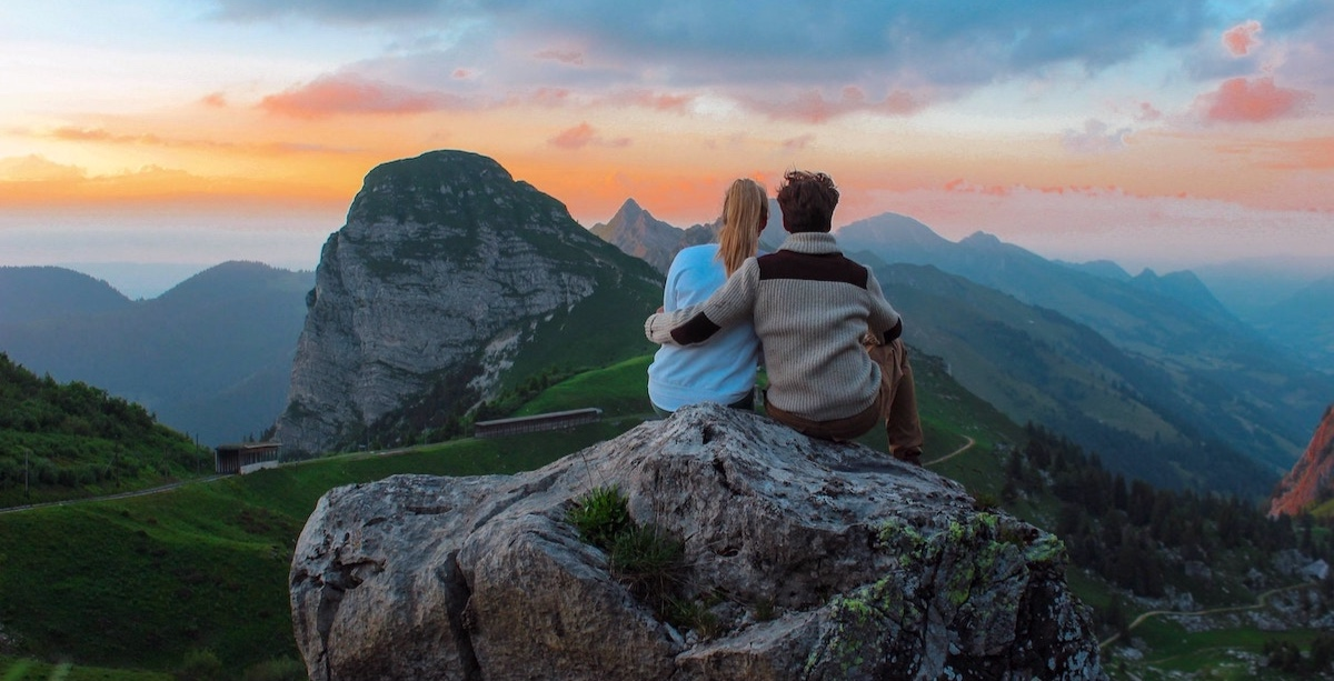 man-and-woman-sitting-on-mountain-looking-at-sunset