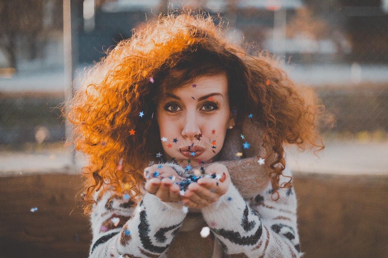 woman-blowing-confetti-natural-hair