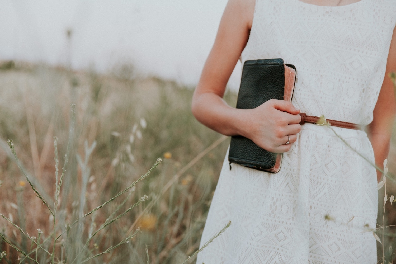 girl-holding-bible-in-field-of-flowers