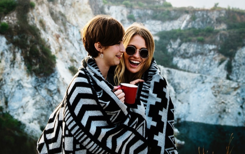 two-friends-hugging-blanket-mountains