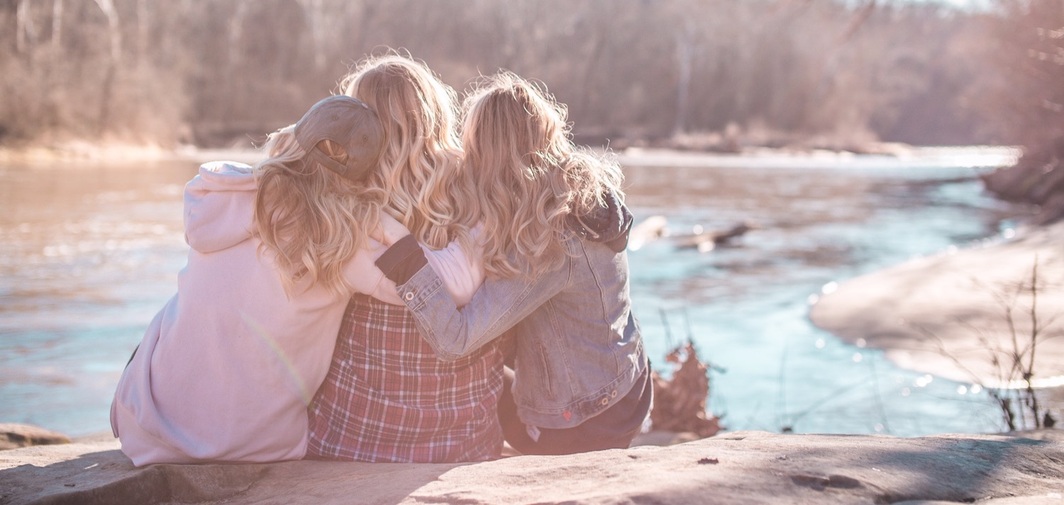 three-friends-hugging-near-river