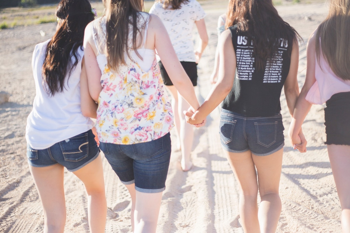 friends-holding-hands-walking-on-the-beach
