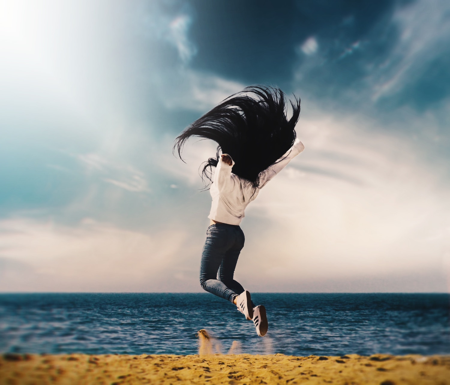 girl-jumping-for-joy-ocean-background