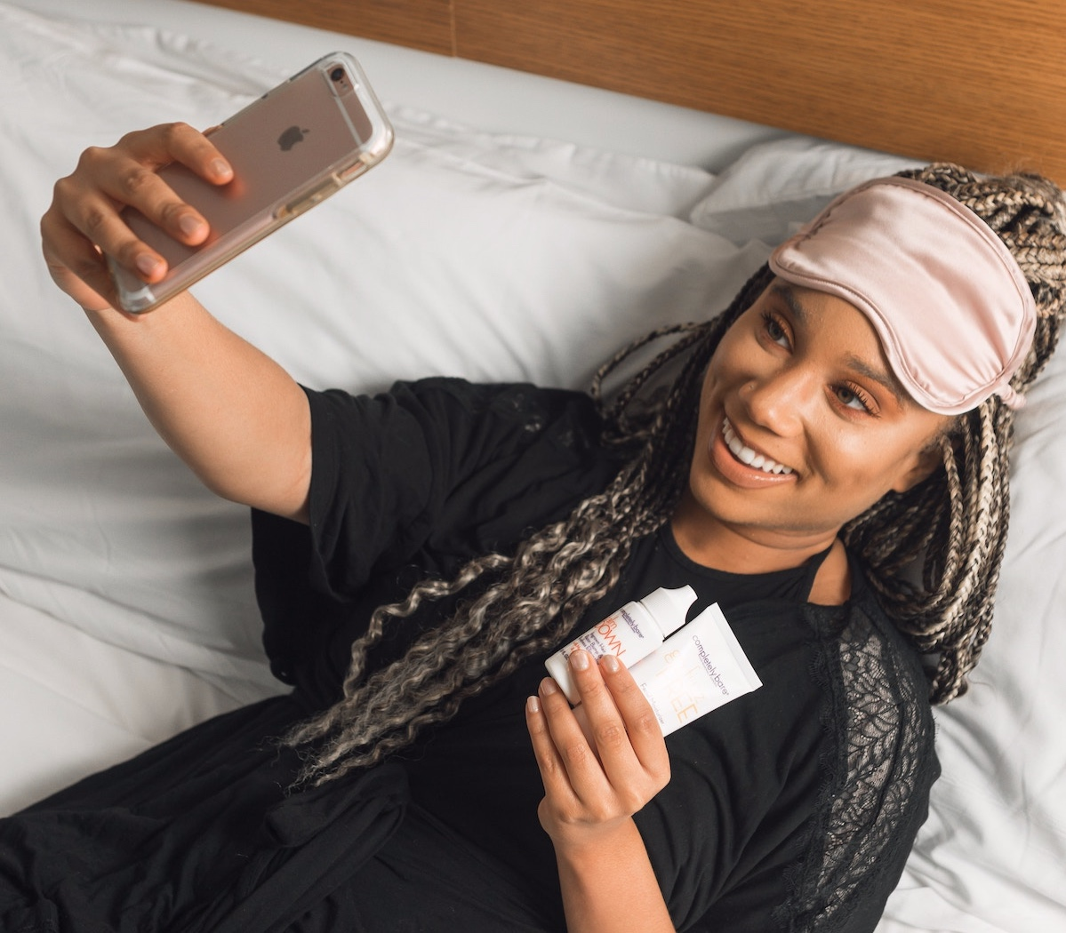 woman-taking-selfie-with-skincare-products