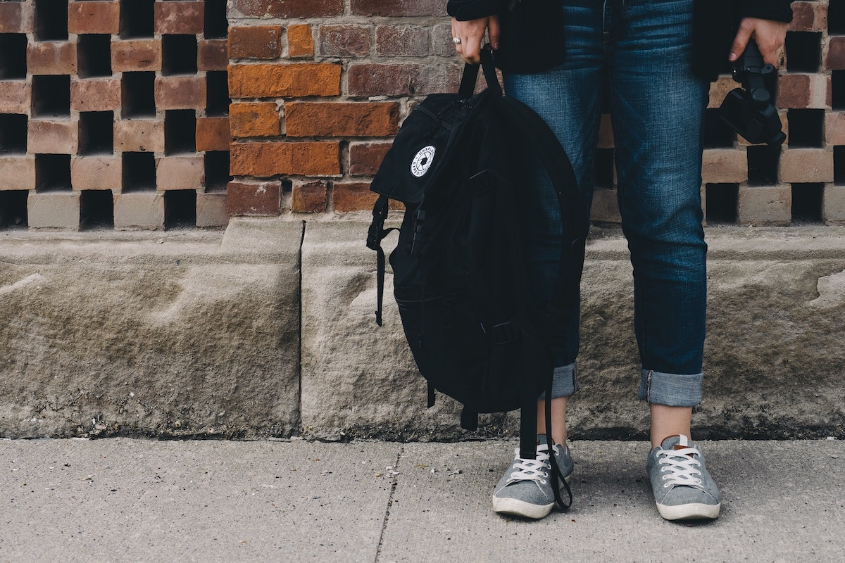 student-holding-backpack
