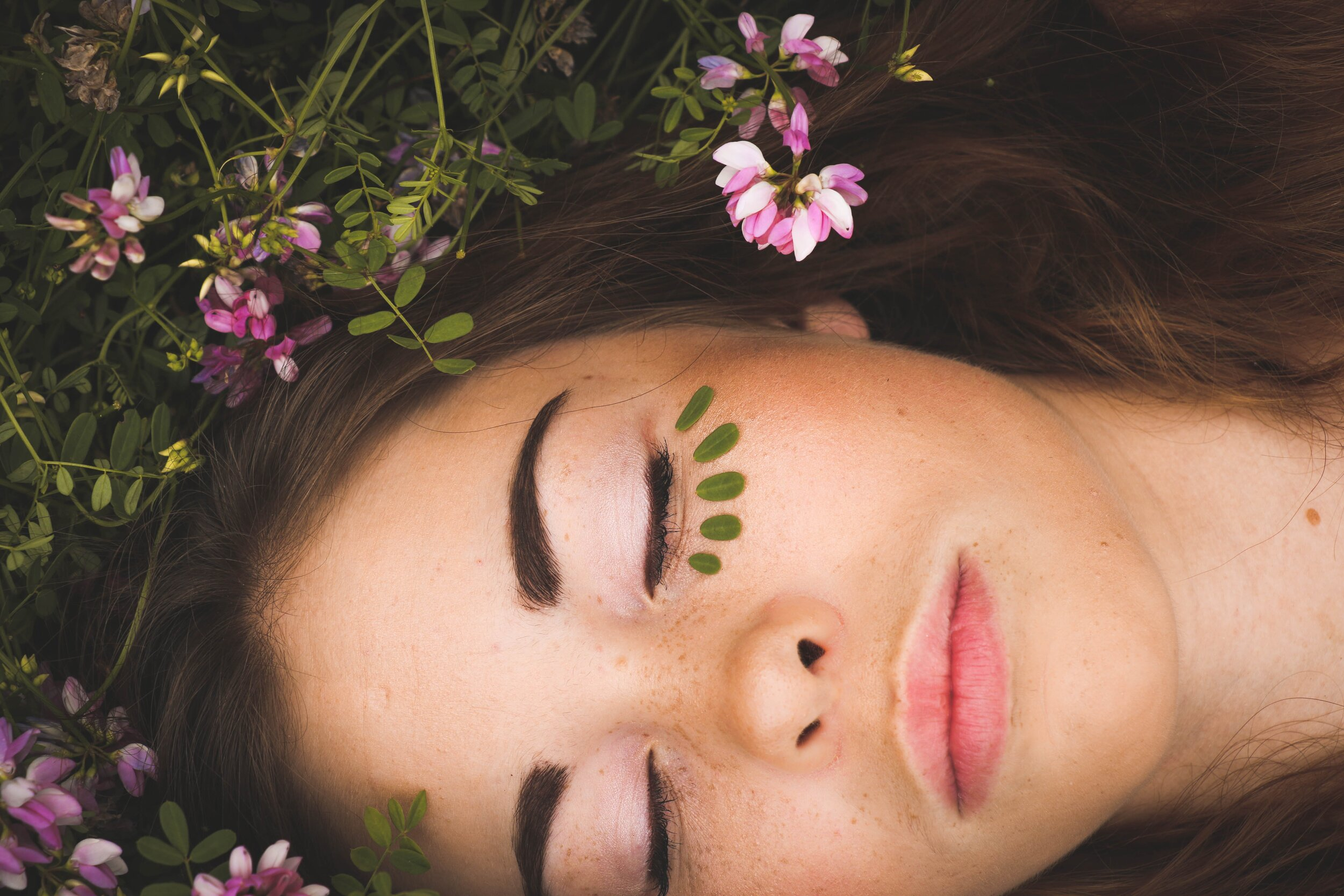 young-teenage-girl-laying-in-grass-flowers