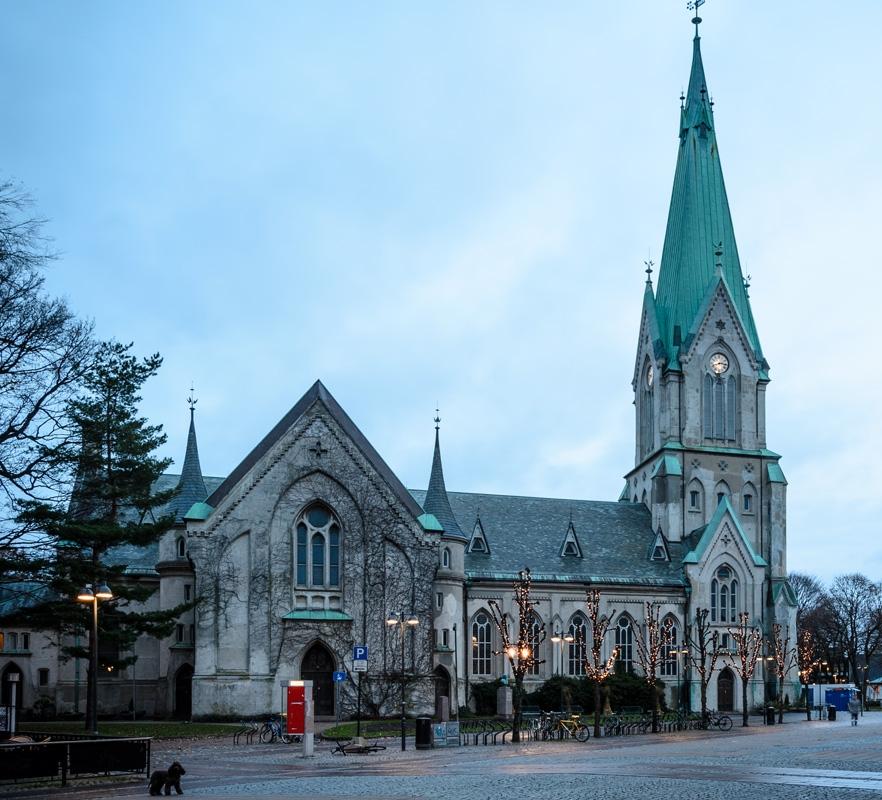 Domkirka - Midt i hjertet av byen, ligger Domkirka. Den sto ferdig i 1885. Med sitt 70 meter høye tårn, føles det som at den står der og passer på oss. Og kirkeklokkene passet egentlig litt på folk i gamledager.I Christian IVs tid, sto det en mindre kirke på Torvet. Den hadde to klokker i tårnet, Storklokka og Lilleklokka. Nesten ingen hadde klokke selv, så kirkeklokkene hjalp folk med å holde tida. Klokka seks om morgenen fortalte Lilleklokka at barna måtte stå opp og gjøre seg klare til skolen. Og hver kveld klokka åtte om vinteren, og ni om sommeren, fortalte den at alle barn i byen måtte gå hjem og legge seg.