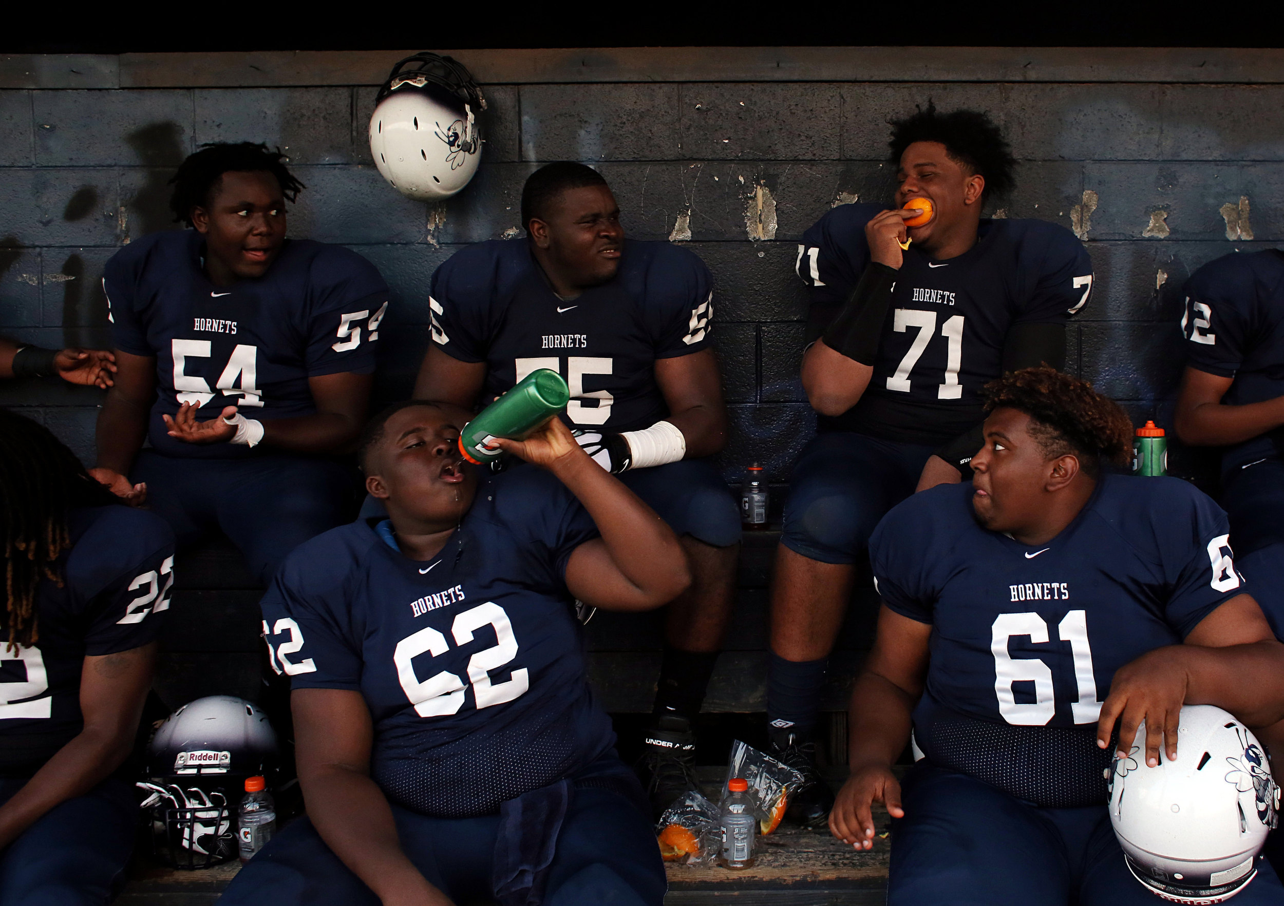 Hillside's Isreal Hinton, from left, Nick Campbell, Shamon Mercier, and Rashad Bailey sit with teammates in a baseball dugout during halftime of their football game against Southern High School on Monday night, Sept. 5, 2016, at Hillside High School.