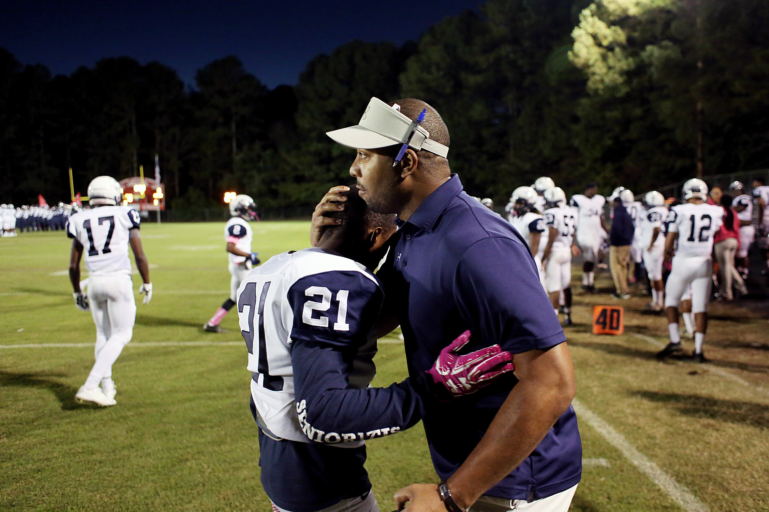 Hillside's Zakee Simmons is embraced by a coach prior to a game against Charles E. Jordan High School on Friday, October 28, 2016, at Jordan High School. Hillside won, 42-14.