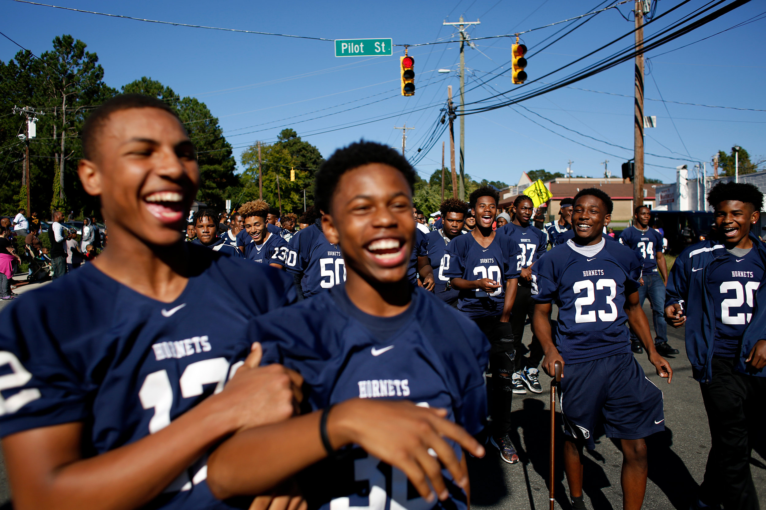 Arm in arm, Hillside's Randy Trice Jr., left, and Deshaun Mitchell walk down Fayetteville Street with teammates during the school's annual homecoming parade, Sunday afternoon, Oct. 9, 2016, in Durham, N.C. The parade wound its way down Fayetteville Street, from East Lawson Street to the high school.
