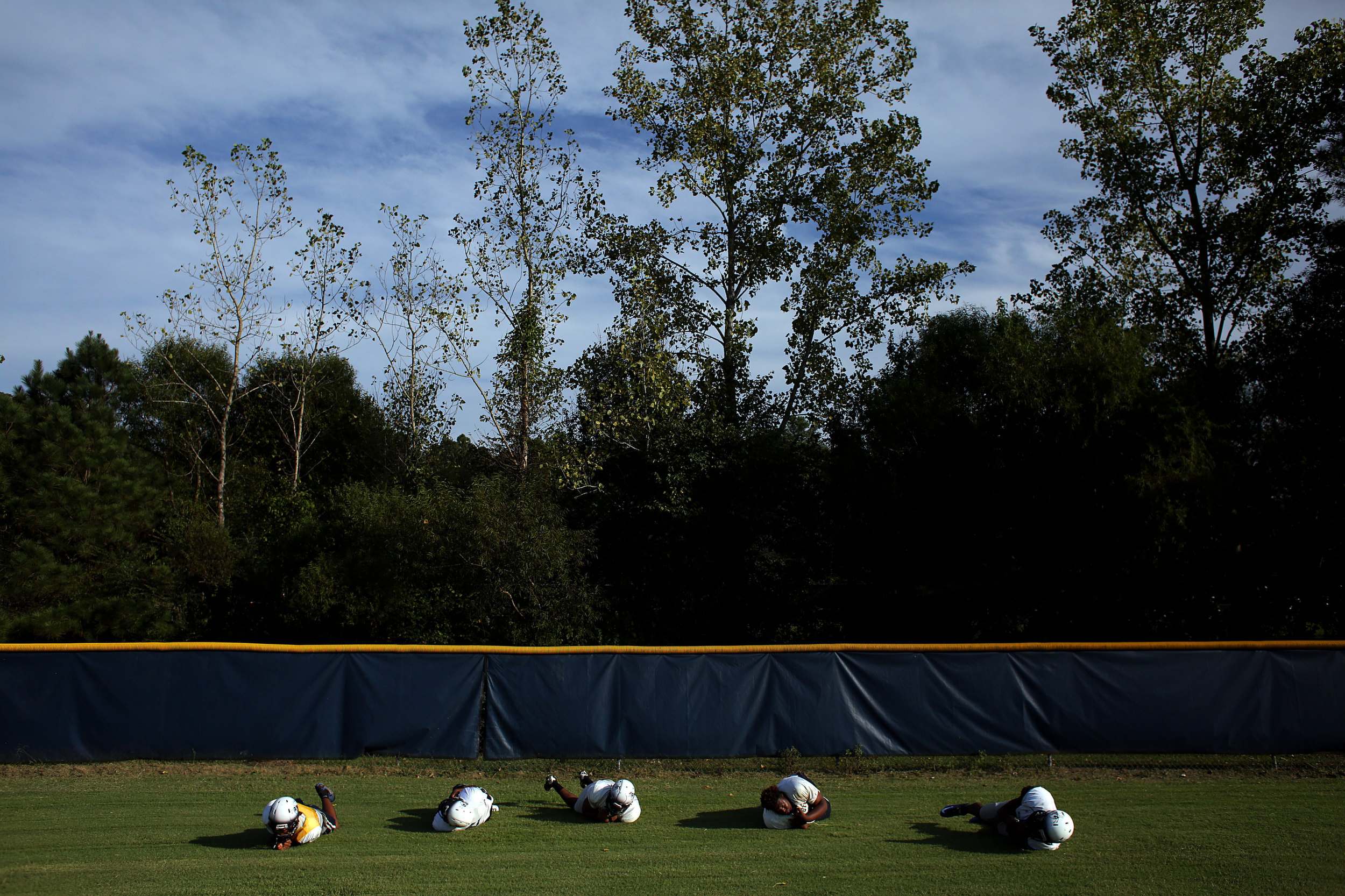Hillside players roll across a baseball outfield as part of punishment for being late to practice, Sept. 14, 2016, at Hillside High School.